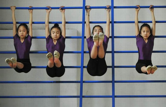 Students stretch during a training session at a gymnastic course